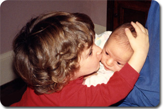 Julie gently kissing baby Andrew