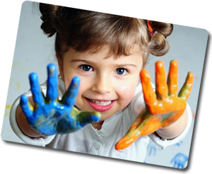young girl holding up hands covered with fingerpaint